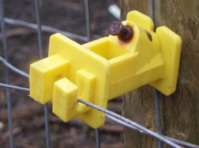 This is a cheap plastic fence insulator meant for nailing to a wooden fencepost. I didn't take this picture, I found it somewhere but it's about what I've got. Note; most insulators are meant for metal posts instead of wood. Buy the right kind.